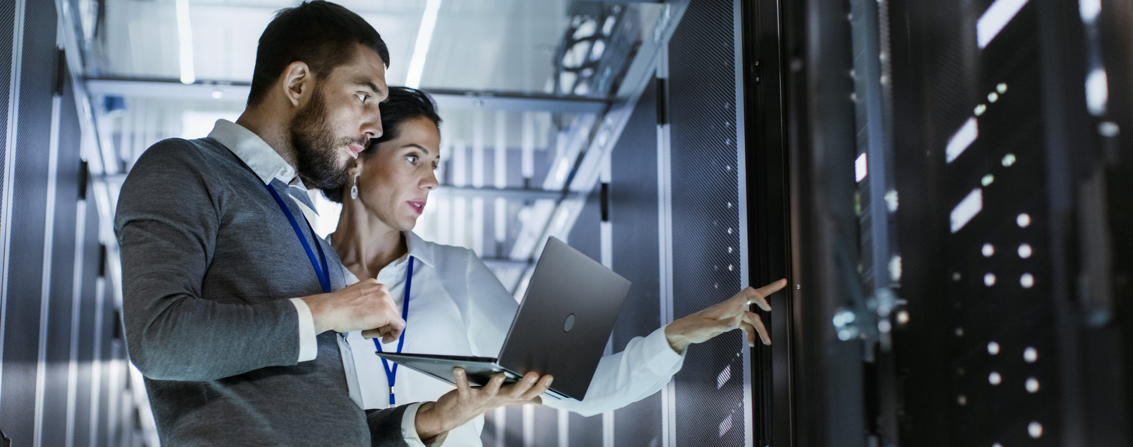 Photo of Male IT Specialist Holds Laptop and Discusses Work with Female Server Technician. They're Standing in Data Center, Rack Server Cabinet is Open.